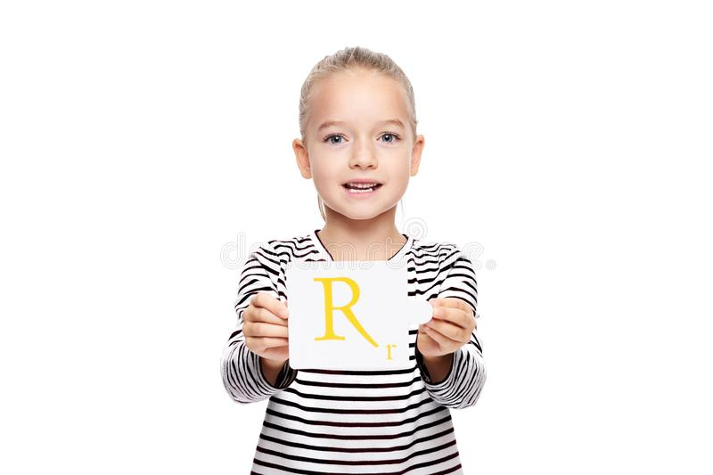 Young girl holding a card with letter R. Speech therapy concept on white background. Correct pronounciation and articulation. Young girl holding a card with stock photos
