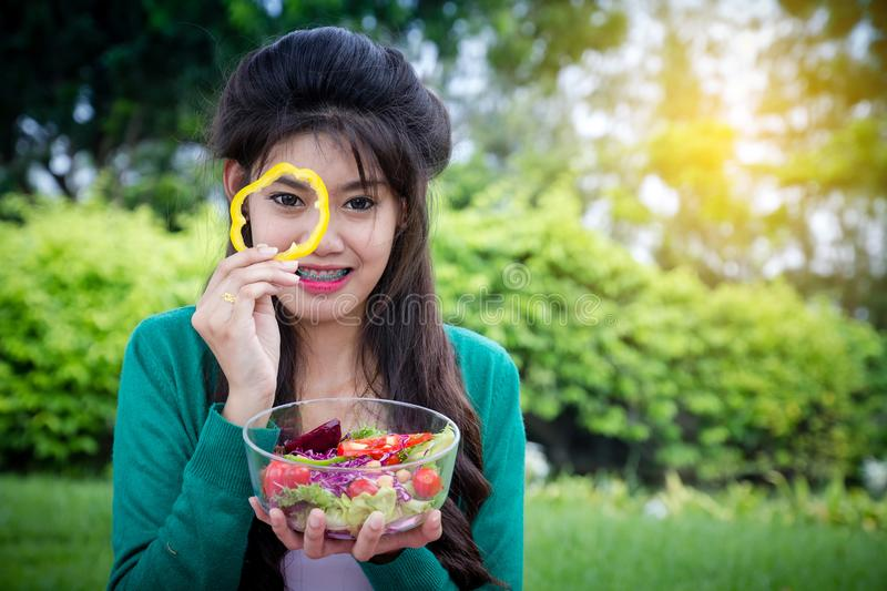 Young girl holding coloful fruits salad bowl in public park with stock images
