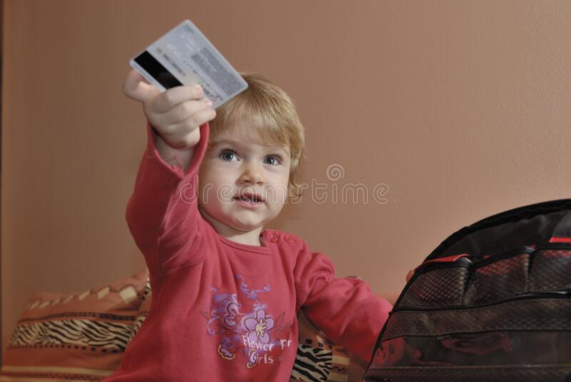 Young girl holding credit card. A portrait of a young girl holding a credit card stock images
