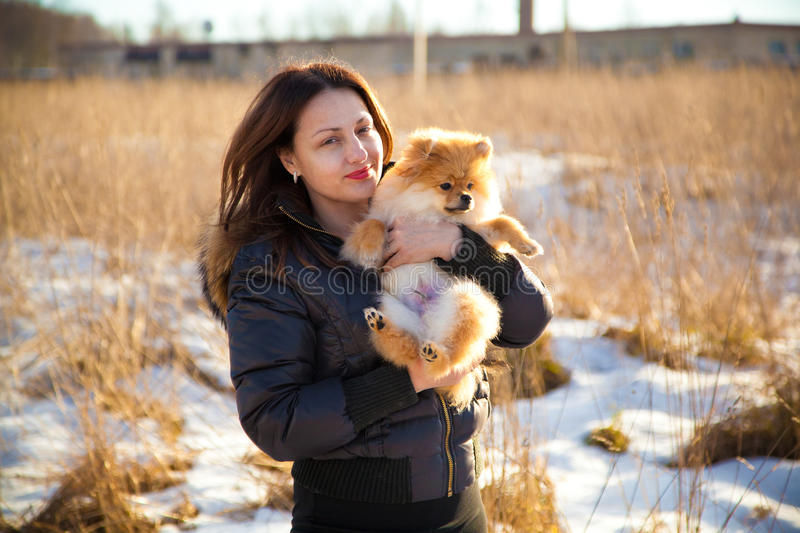 Young girl holding a dog Spitz royalty free stock photography