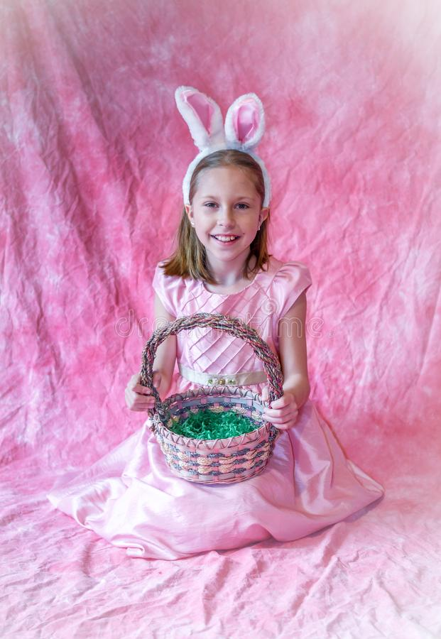 Young girl holding an easter basket and wearing bunny ears. Full length portrait of a young girl  in her Easter dress, holding an easter basket and wearing bunny stock photography