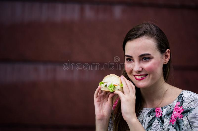 Young girl holding fast food burger, American unhealthy calories stock image