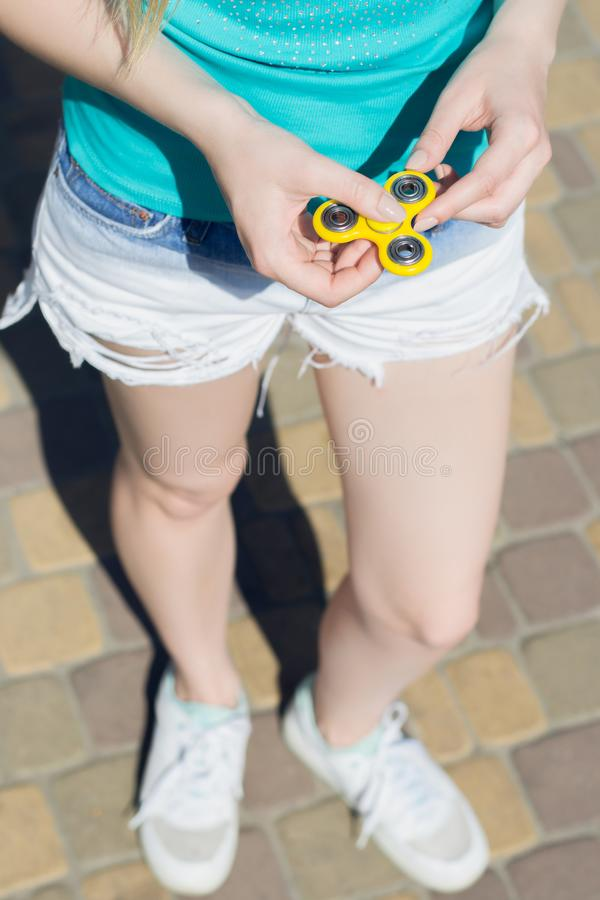 Young girl holding fidget spinner in hands while having a walk outdoors addiction game gamer play player yellow thing toy cropped stock photography