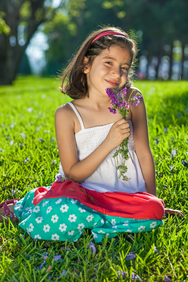 Young Girl Holding Flowers sitting on Grass royalty free stock image