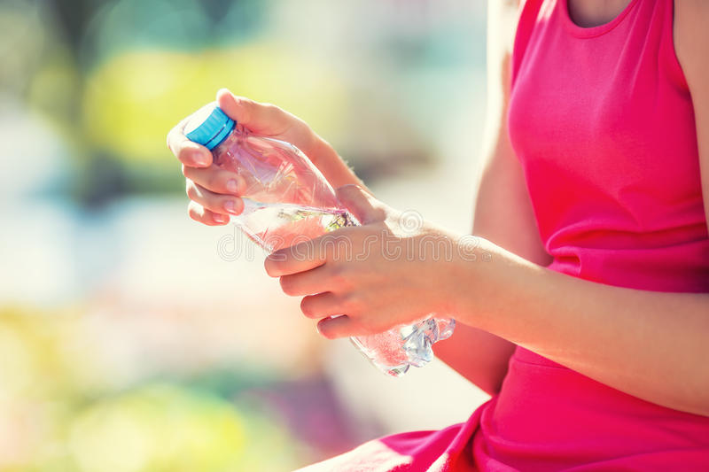 Young girl holding in hand bottle water on a hot summer day royalty free stock images