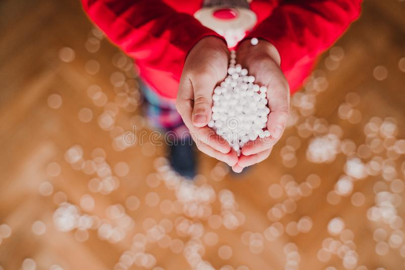 Young girl holding with hands artificial snow flakes at home. Christmas concept. Waiting, floor, toddler, kid, blow, blowing, fly, white, happy, cold, red royalty free stock photography