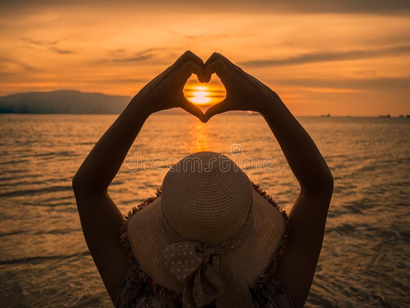Young girl holding hands in heart shape framing setting sun at sunset royalty free stock image