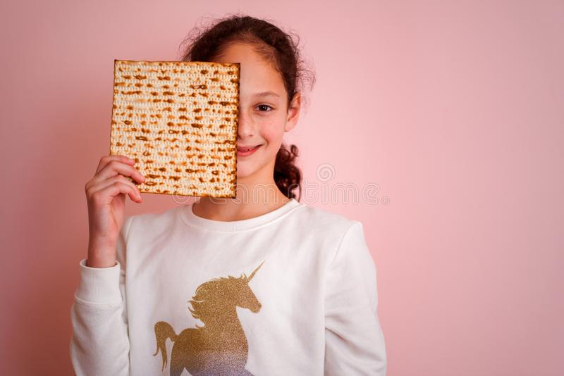 Young girl holding matzah or matza. Jewish holidays Passover invitation or greeting card.Selective focus.Copy space. royalty free stock photography