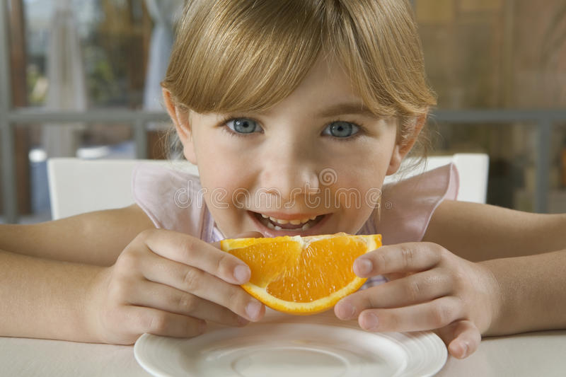 Young girl holding orange slice. Young girl at the table holding an orange slice stock images