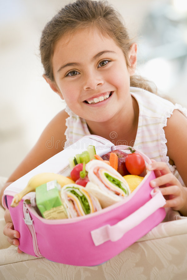 Young girl holding packed lunch in living room stock images