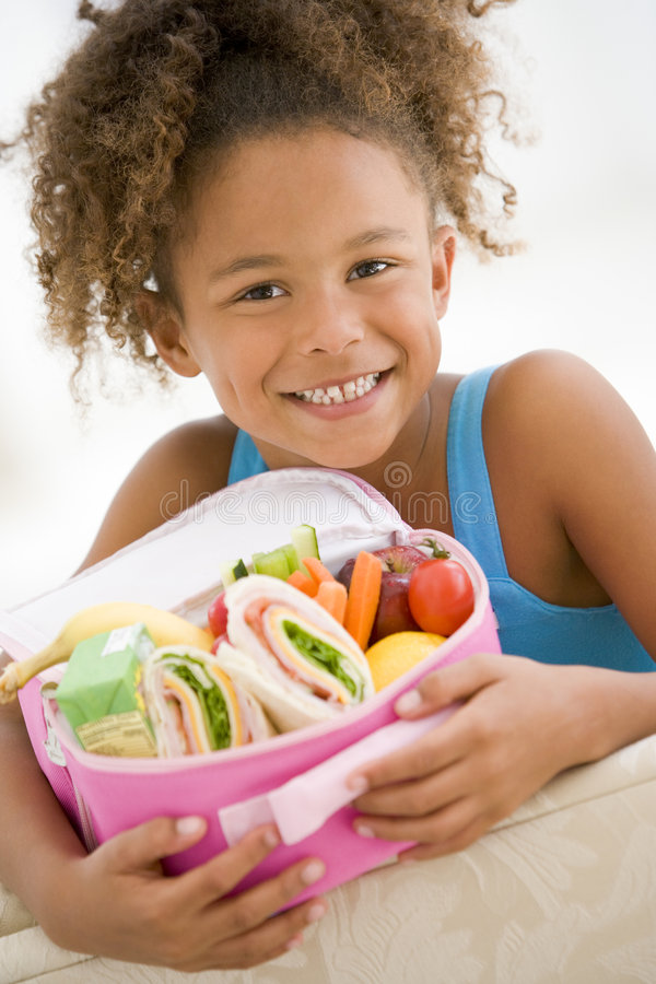 Young girl holding packed lunch in living room royalty free stock images