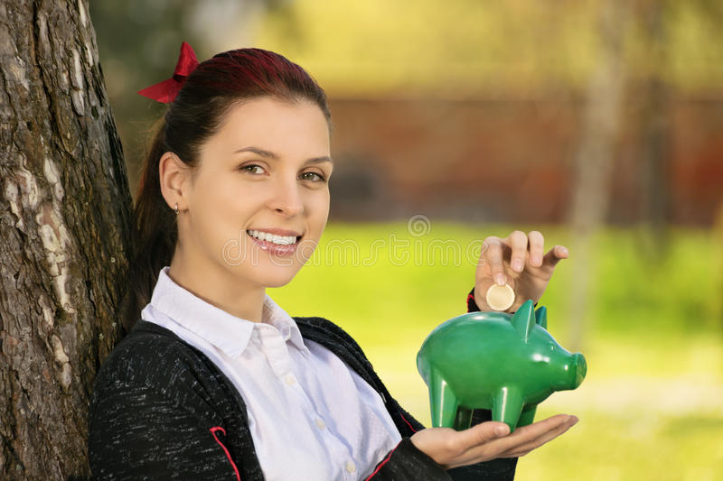 Young girl holding a piggy bank. Saving during sunny days so when the rainy ones come. Beautiful young female student leaning on a tree in the park, putting a royalty free stock images