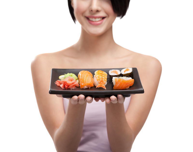 Young girl holding plate of sushi and smiling royalty free stock image