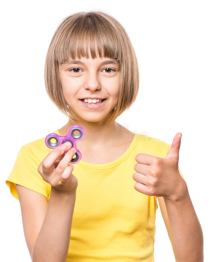 Little girl with spinner toy. Young girl holding popular fidget spinner toy - close up portrait. Happy smiling child playing with Spinner and making thumb stock photo