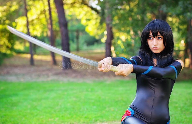 Young girl holding samurai sword. Original cosplay character royalty free stock images