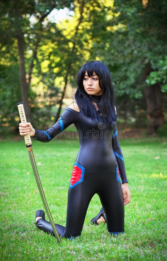 Young girl holding samurai sword. Original cosplay character royalty free stock photo