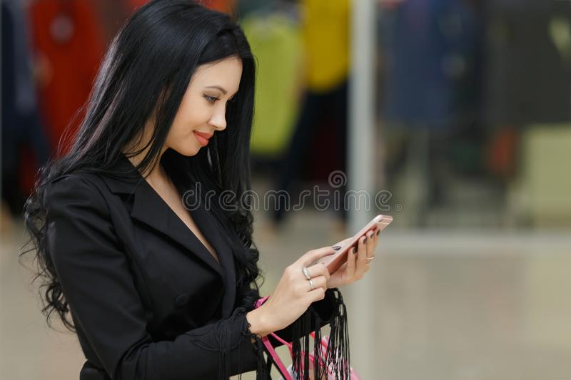 Young girl is holding shopping bags and using a smart phone in mall royalty free stock images
