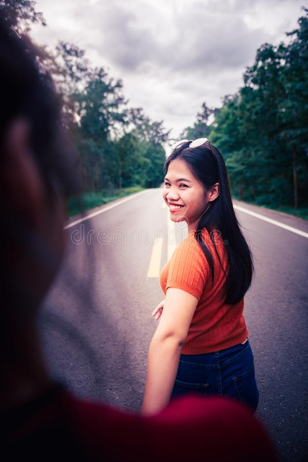 Young girl holding sister hand while leading her on road outdoor. Travel on countryside concept. Closeup Young girl holding sister hand while leading her on road stock photography