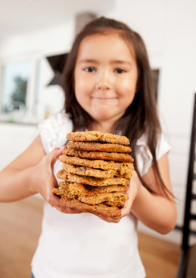 Young Girl Holding Stack of Cookies royalty free stock photos