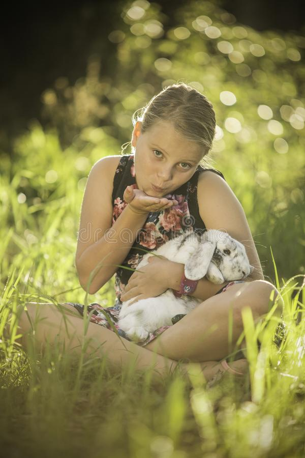 Young girl is holding white rabbit stock photo