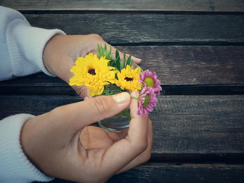 Young girl holds flower in small vase on rustic wooden table background. Copy space for text or design. stock photos