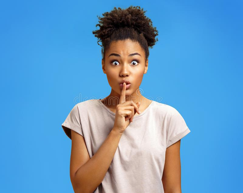 Young girl holds forefinger on lips, has mysterious expression, shows silence gesture royalty free stock image