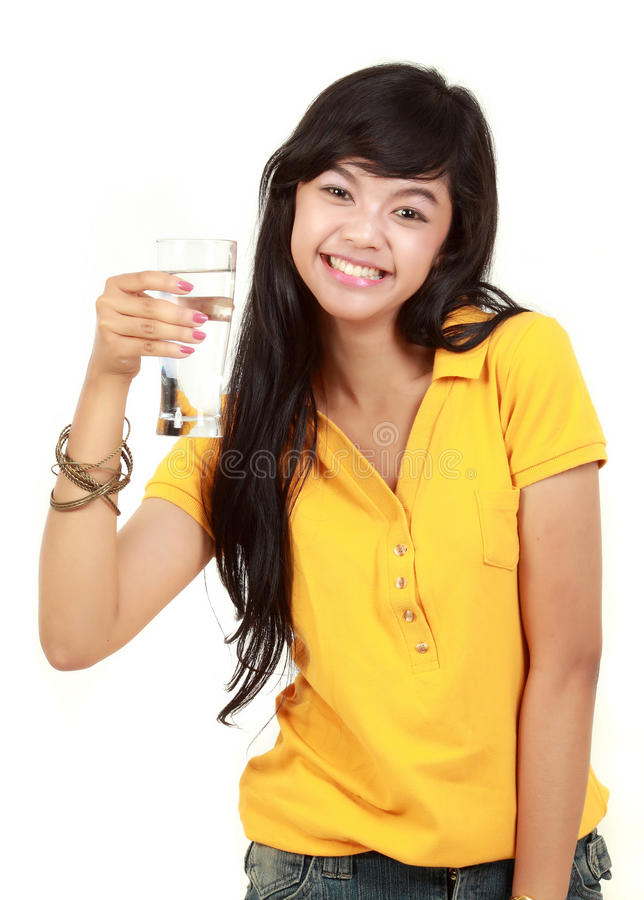 Young girl holds a glass of water. Happy Beautiful young girl holds a glass of water stock photography