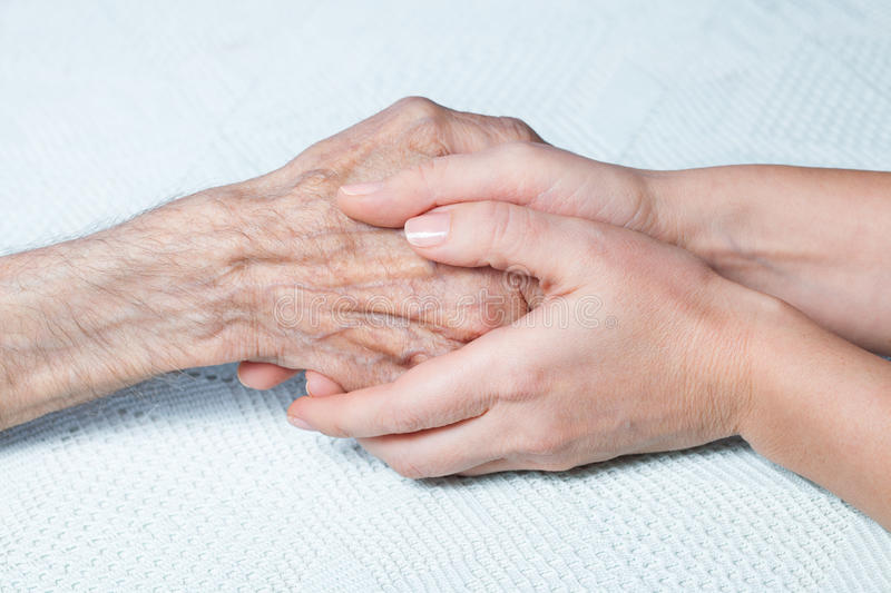 A young girl holds hands of an old man stock photos