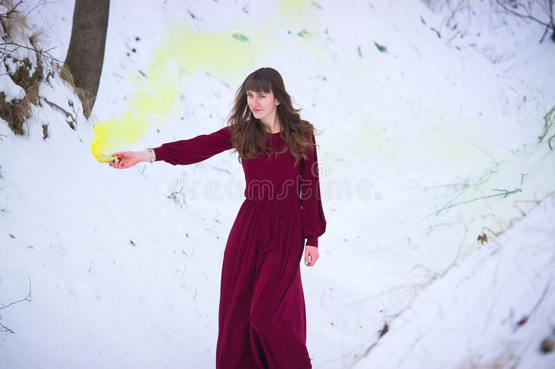 Young girl holds in her hand colorful smoke of many colors royalty free stock photography