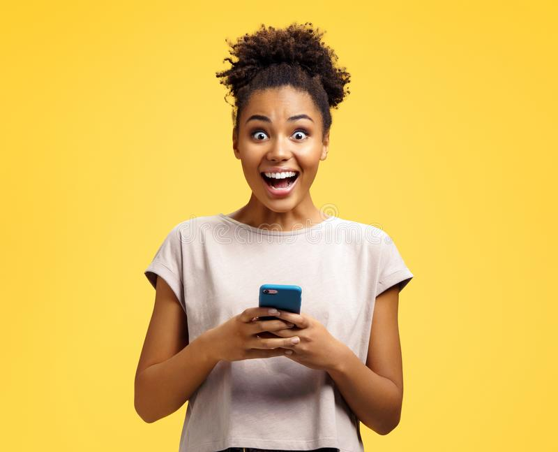 Young girl holds phone, happy to receive notification. Photo of african american girl wears casual outfit on yellow background. Emotions and pleasant feelings stock photography