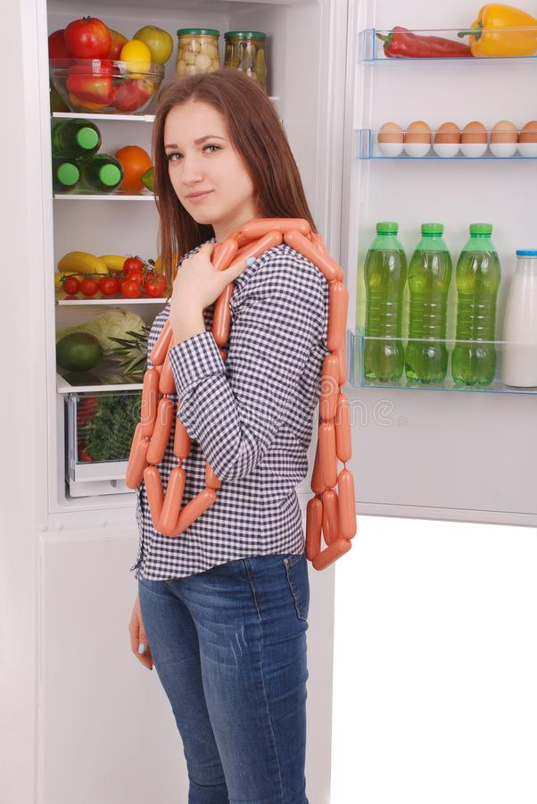 Young girl holds sausages on the refrigerator background royalty free stock images