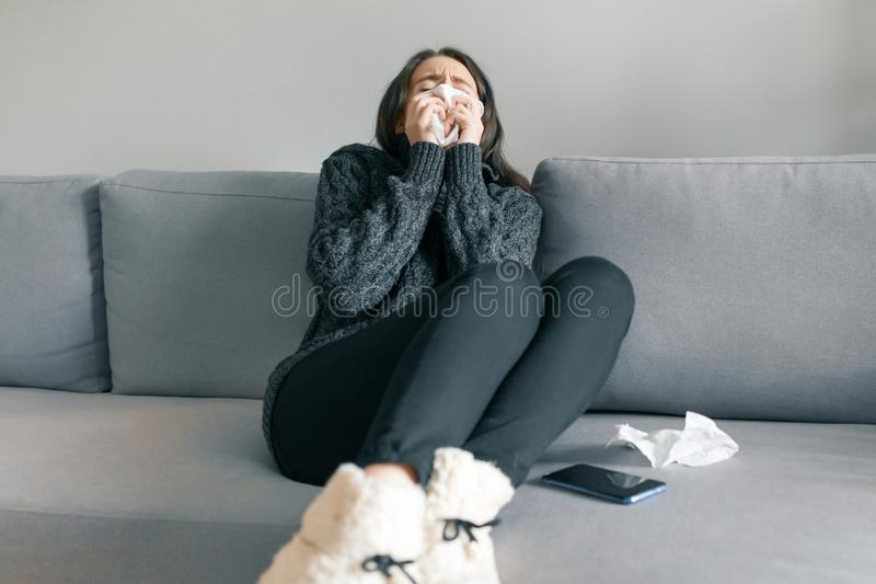 Young girl at home on the sofa in warm knitted sweater with handkerchief, sneezes. Flu and cold season.  royalty free stock images