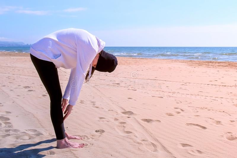 Girl does tilts on sea sand beach fitness outdoor sport exercises on training. Young girl in hoodie, hat and leggings on sea sand beach. She makes squats stock photo