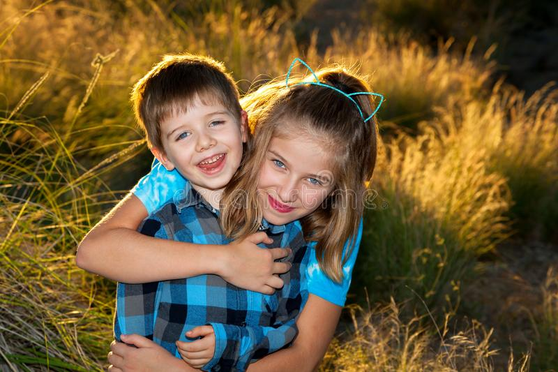 Young Girl Hugs Her Younger Brother From Behind For a Portrait i stock photos