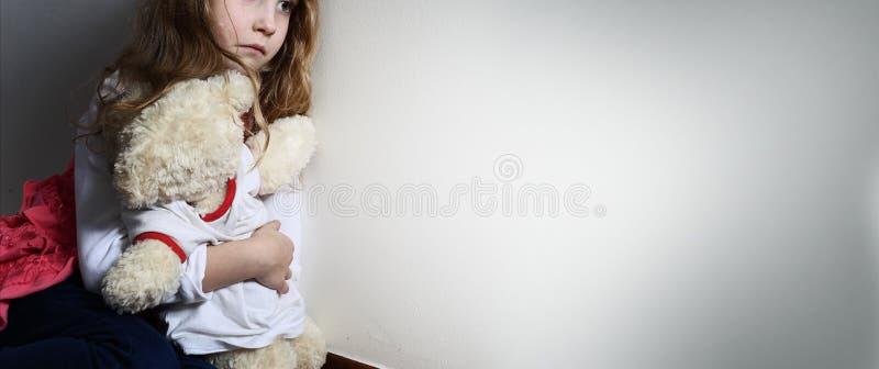 Young girl hugs a teddy bear royalty free stock image