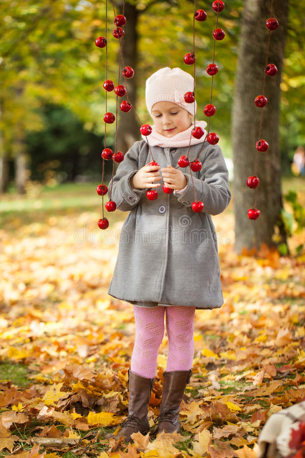 Free Young Girl In Autumn Park With Apple Garland Royalty Free Stock Photo - 76503615