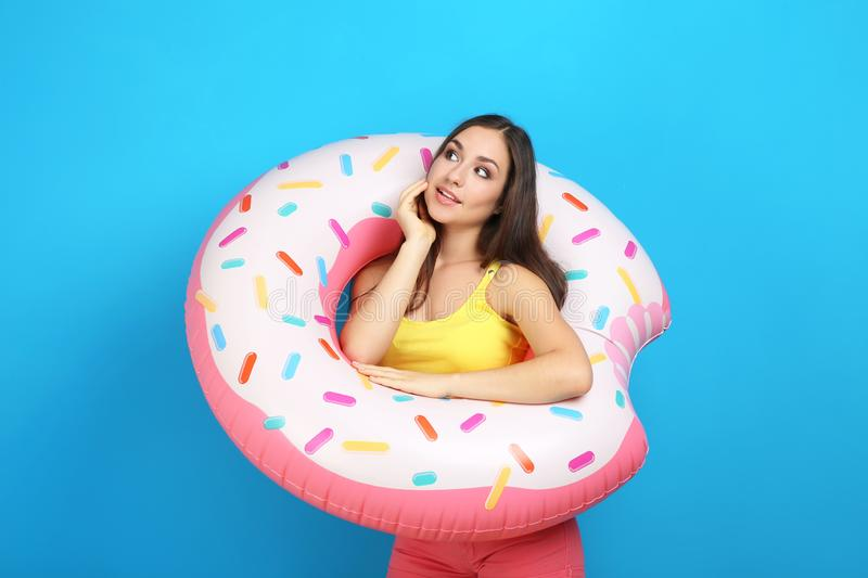 Young girl with inflatable donut. On blue background stock image