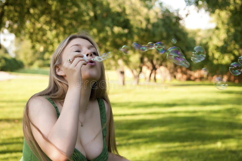 Young girl inflating soap bubbles stock photos