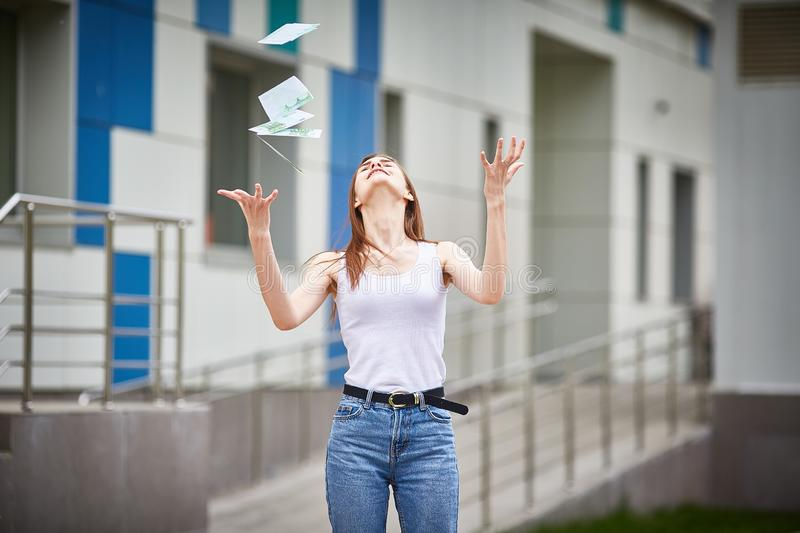 Girl catches falling euro banknotes royalty free stock image