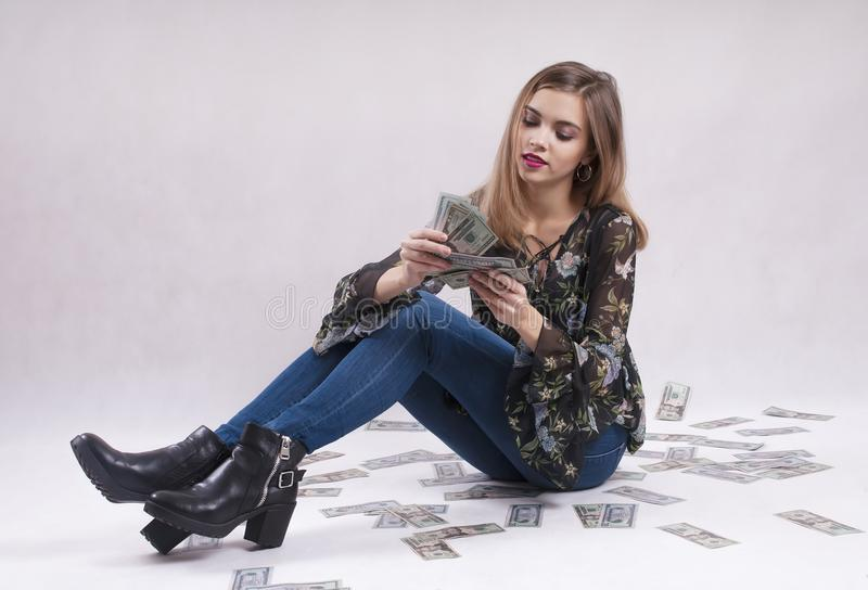 Young girl in jeans sits with dollars financial royalty free stock image
