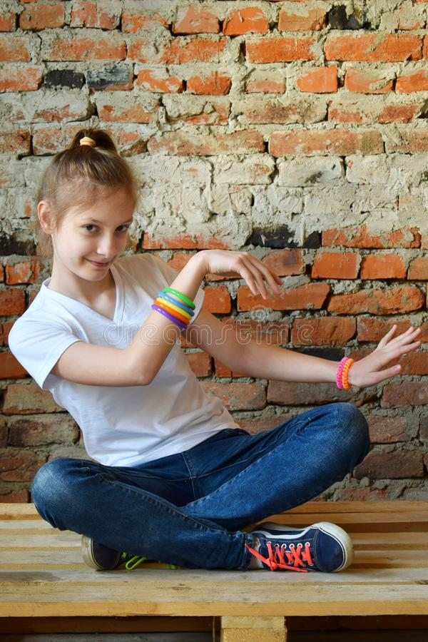 Young girl in jeans and white T-shirt is sitting on the floor and dance. Concept portrait of a pleasant friendly happy  teenager. Young girl in jeans and white T royalty free stock photography