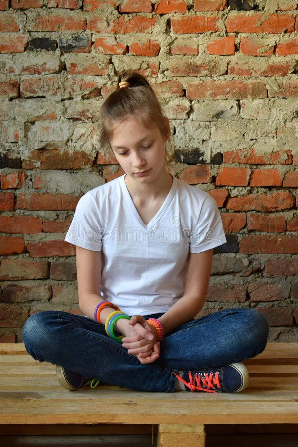 Young girl in jeans and white T-shirt is sitting on the floor and sad. Concept of a non happy teenager. Young girl in jeans and white T-shirt is sitting on the royalty free stock images
