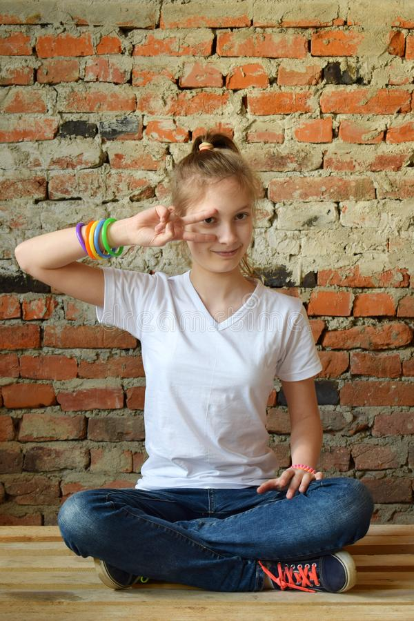 Young girl in jeans and white T-shirt is sitting on the floor and smiling. Concept portrait of a pleasant friendly happy teenager. Young girl in jeans and white royalty free stock photos