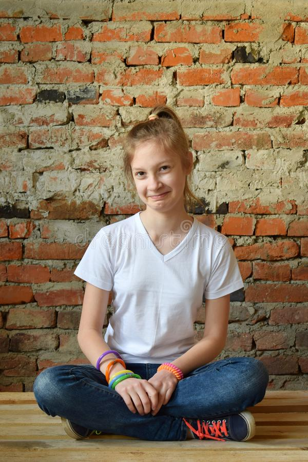 Young girl in jeans and white T-shirt is sitting on the floor and smiling. Concept portrait of a pleasant friendly happy teenager. Young girl in jeans and white royalty free stock photo