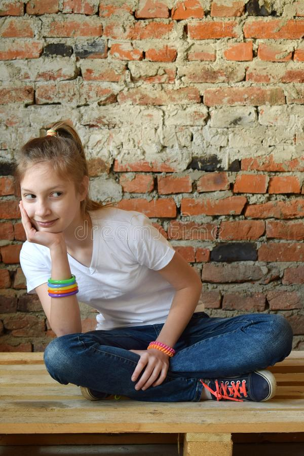 Young girl in jeans and white T-shirt is sitting on the floor and smiling. Concept portrait of a pleasant friendly happy teenager. Young girl in jeans and white stock images
