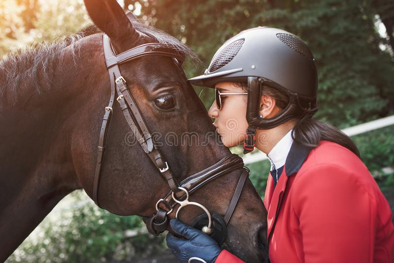 A young girl jockey talking and kissing her horse. She loves the animals and joyfully spends her time in their environment royalty free stock photos