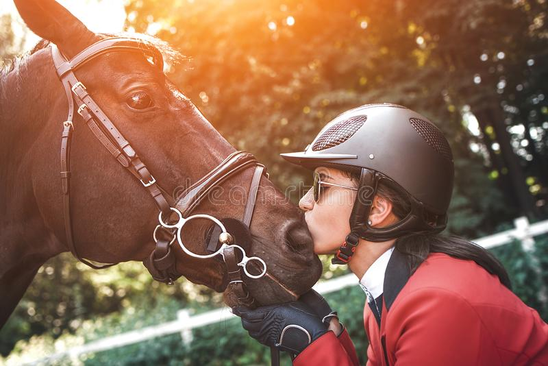 A young girl jockey talking to her horse. She loves the animals and joyfully spends her time in their environment royalty free stock image