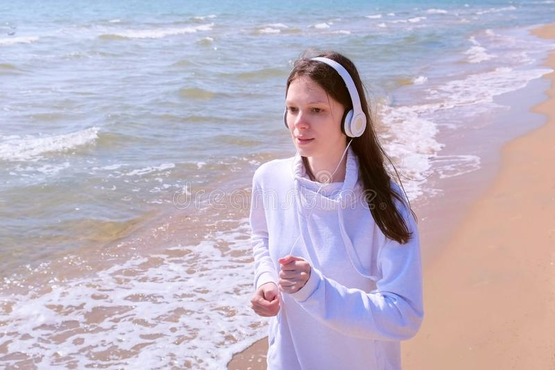 Girl in headphones music jogging at sea sand beach sport run outdoor training. Young girl is jogging at sea sand beach listening music in headphones. She is royalty free stock images