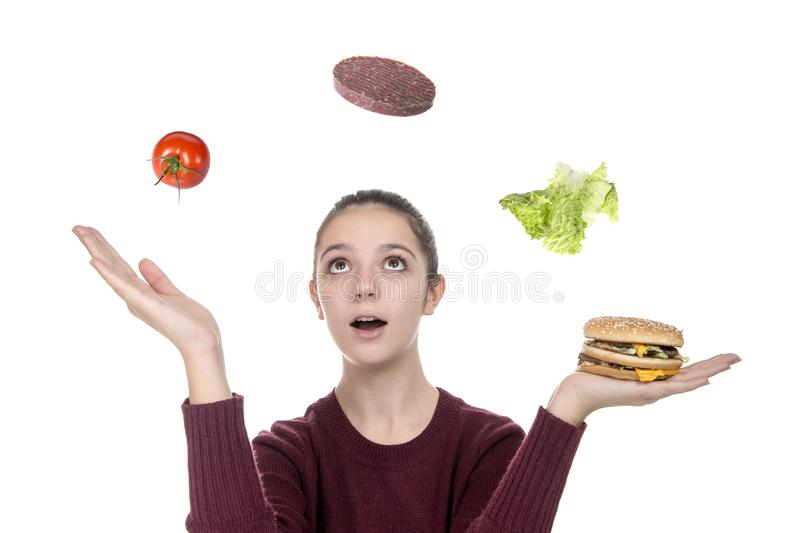 Young girl juggling with hamburger ingredients stock photography
