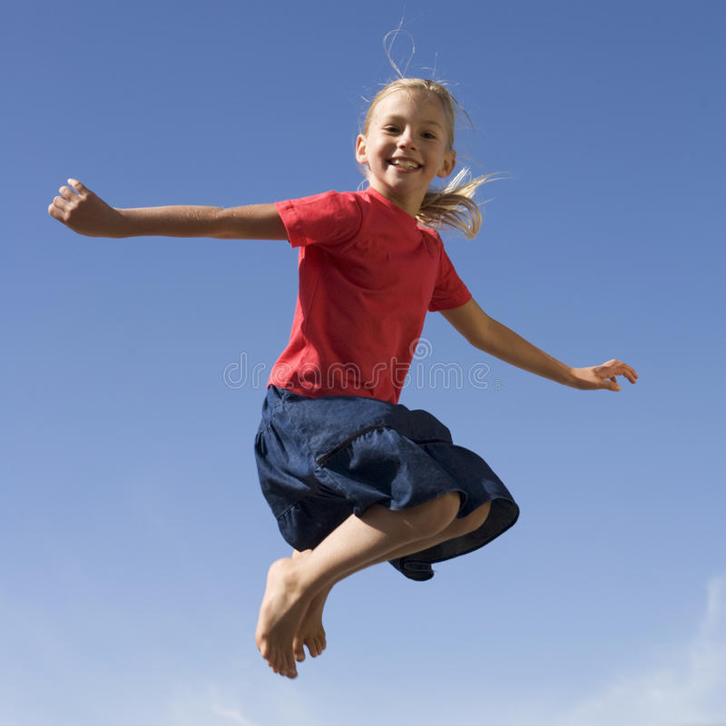 A young girl jumping stock photo